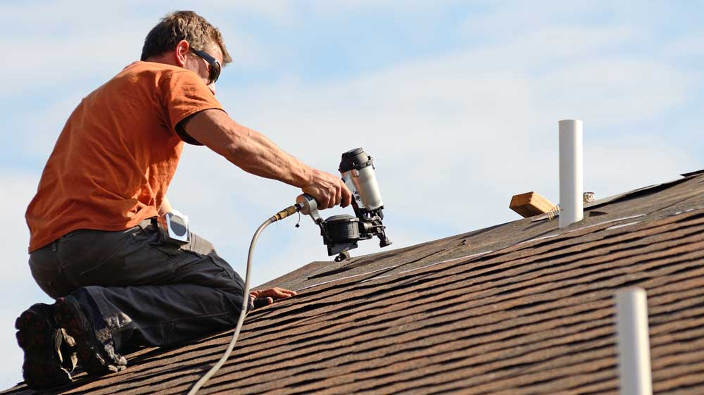 Roofing contractor installing asphalt shingle roof