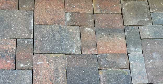 Concrete pavers installed in a pattern with different size bricks