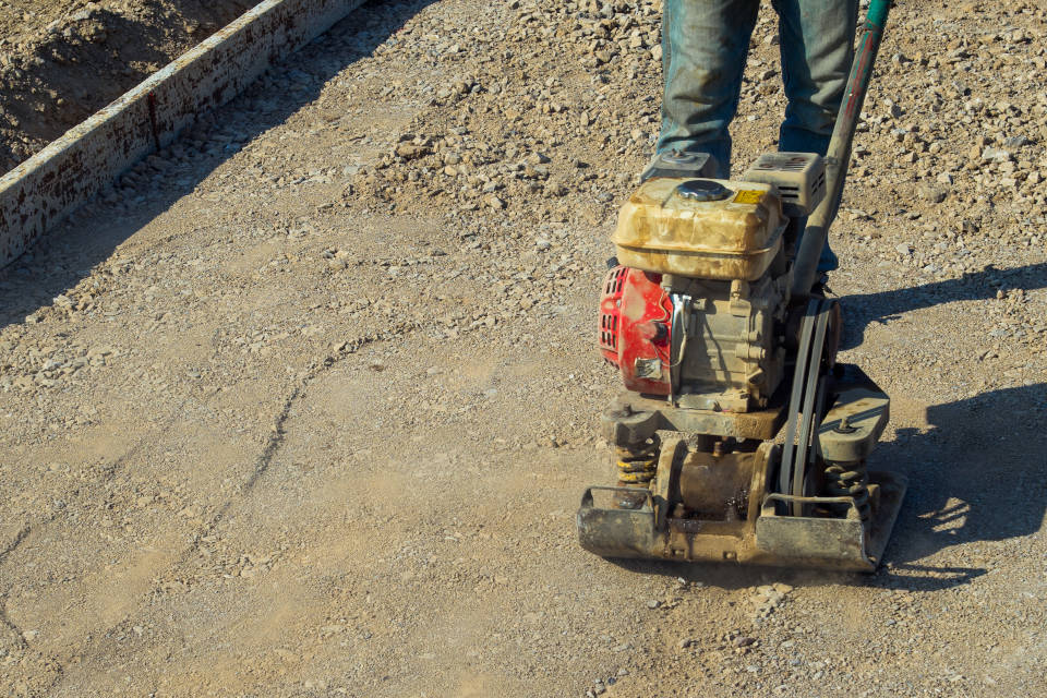 compacting the gravel patio base using a plate compactor