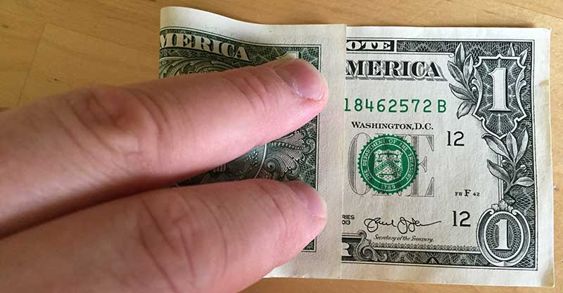 "Fold the dollar bill with the left edge aligning between the N and O in the word ""note"""