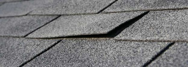 Lifting edge of a roof shingle indicating that the roof should be replaced
