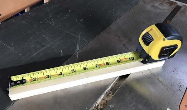 tape measure being used to measure a piece of wood