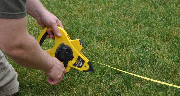 Fence installer using a tape measure to lay out a fence