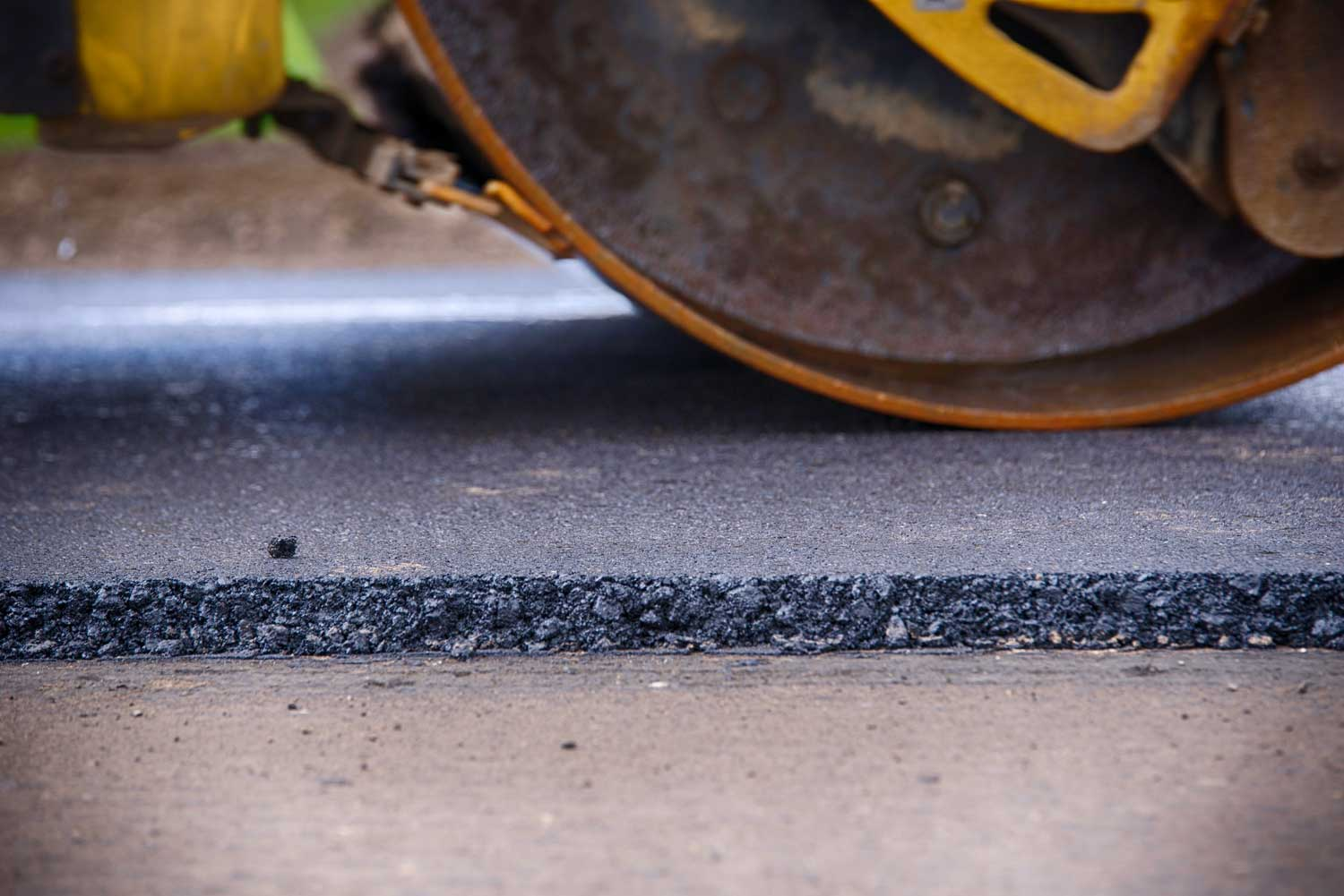 Steamroller compacting and flattening a new asphalt driveway