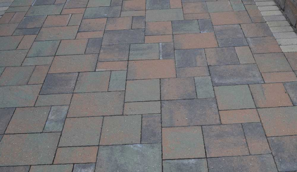 Paver patio constructed using concrete pavers in various colors, shapes, and sizes
