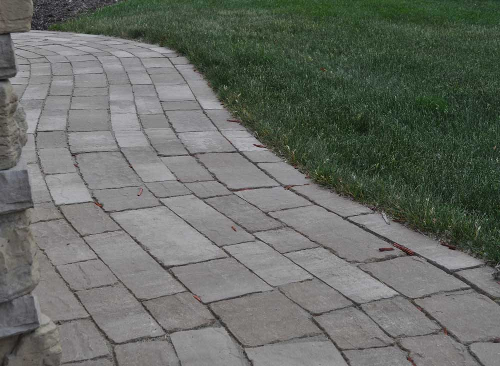 Winding paver walkway constructed using concrete pavers in various textures, shapes, and sizes