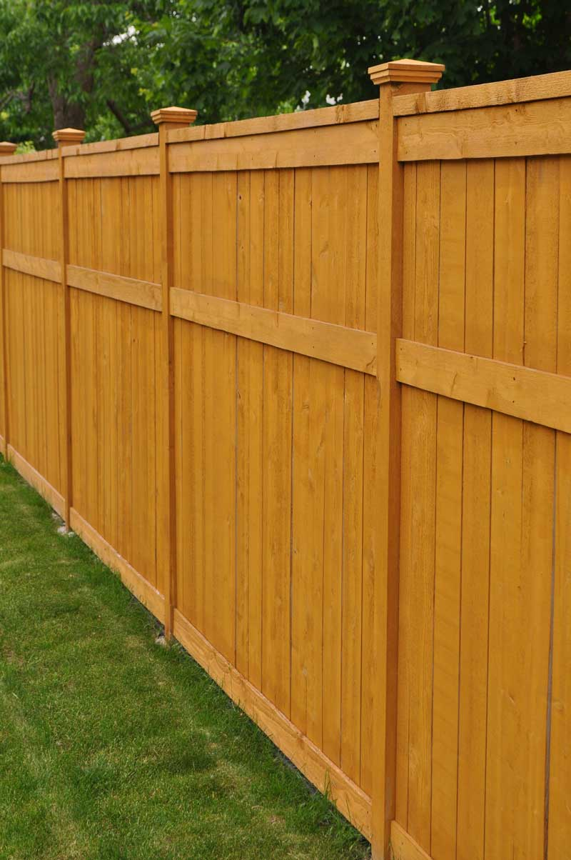 New modern wood privacy fence with a fresh stain finish