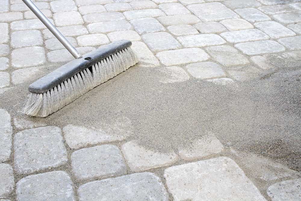 Person sweeping polymeric jointing sand into paver joints to prevent weed growth