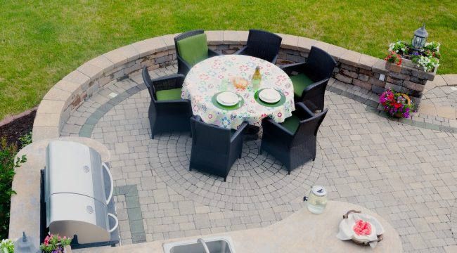 Newly installed paver patio with dining table and grill