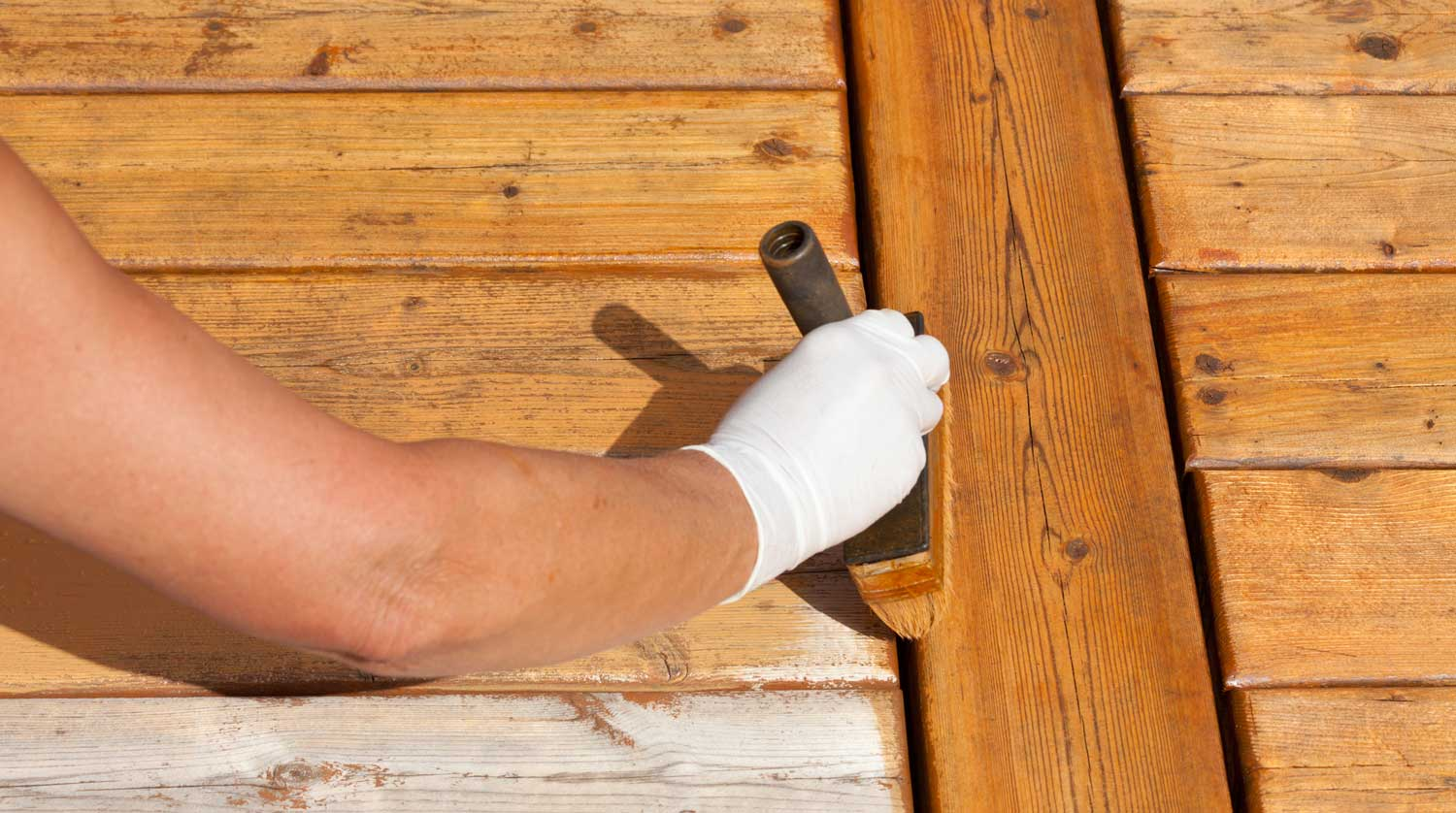 person staining a deck using a paint brush