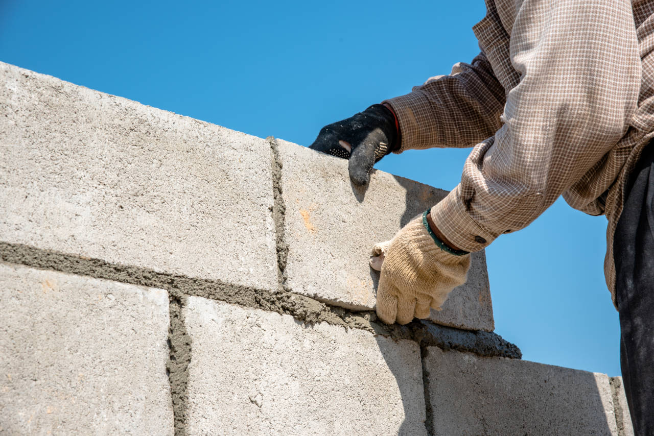 concrete block foundation wall being constructed by a mason