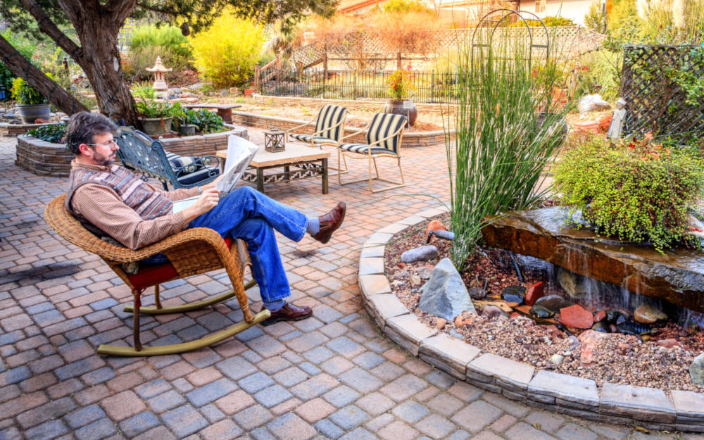 Newly estimated and installed paver patio with person sitting on a chair