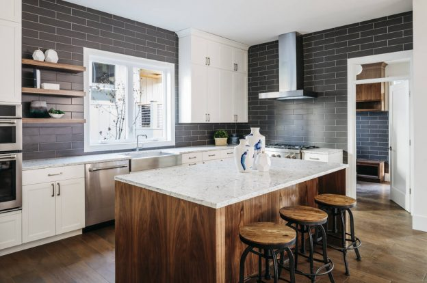 Kitchen with blue tile, a large island, and marble countertops