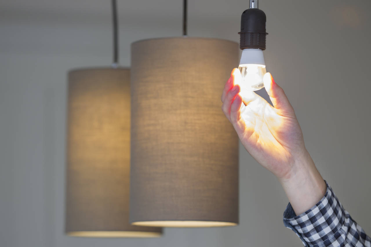 Person installing an LED light bulb in a pendant light fixture