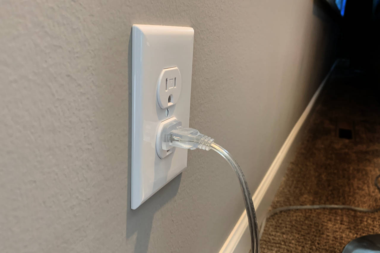 Electrical receptacle on a wall with a lamp cord plugged in