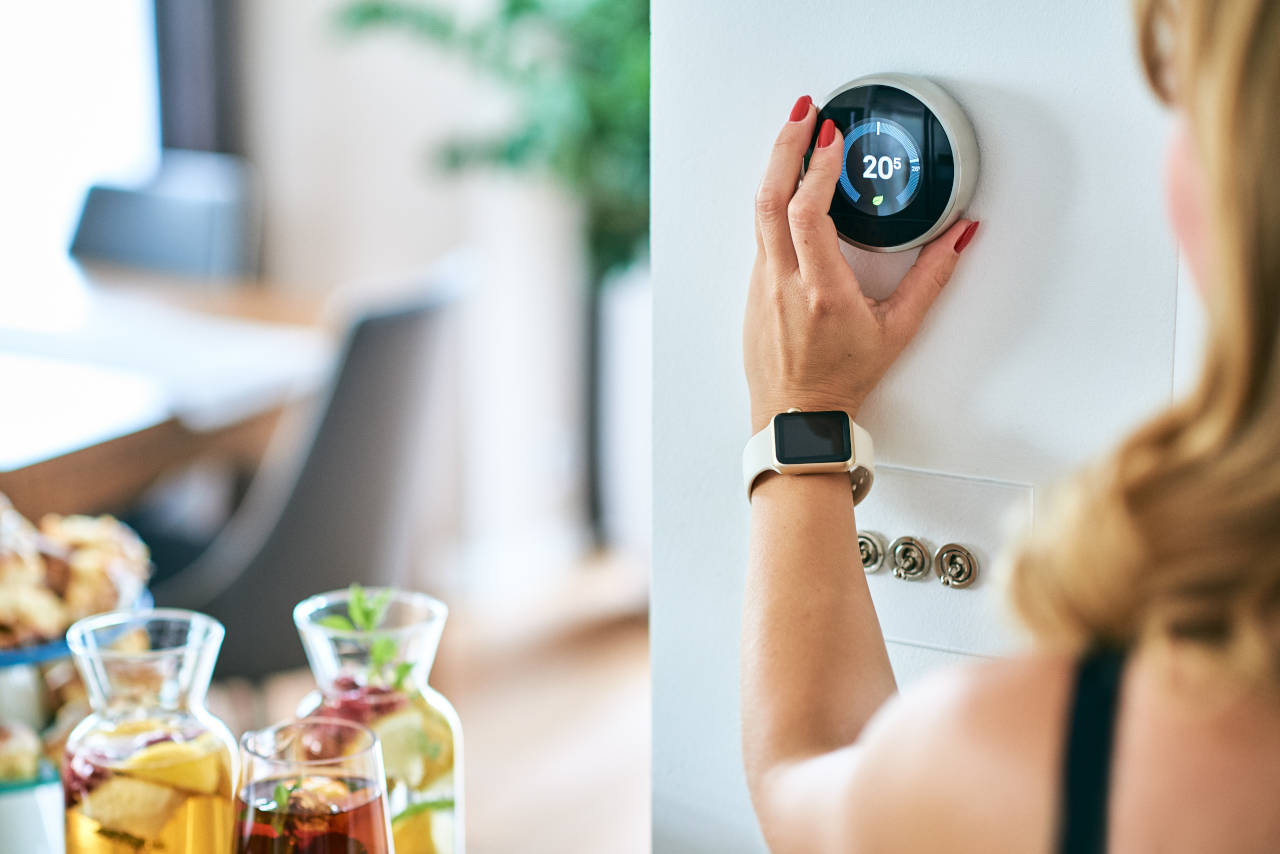 woman adjusting a Nest smart thermostat