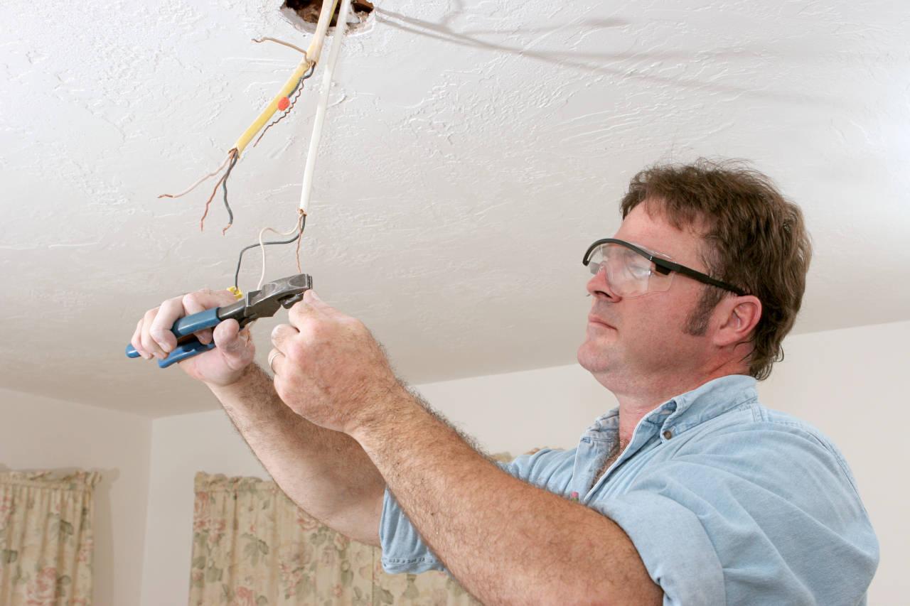 Electrician rewiring a light fixture