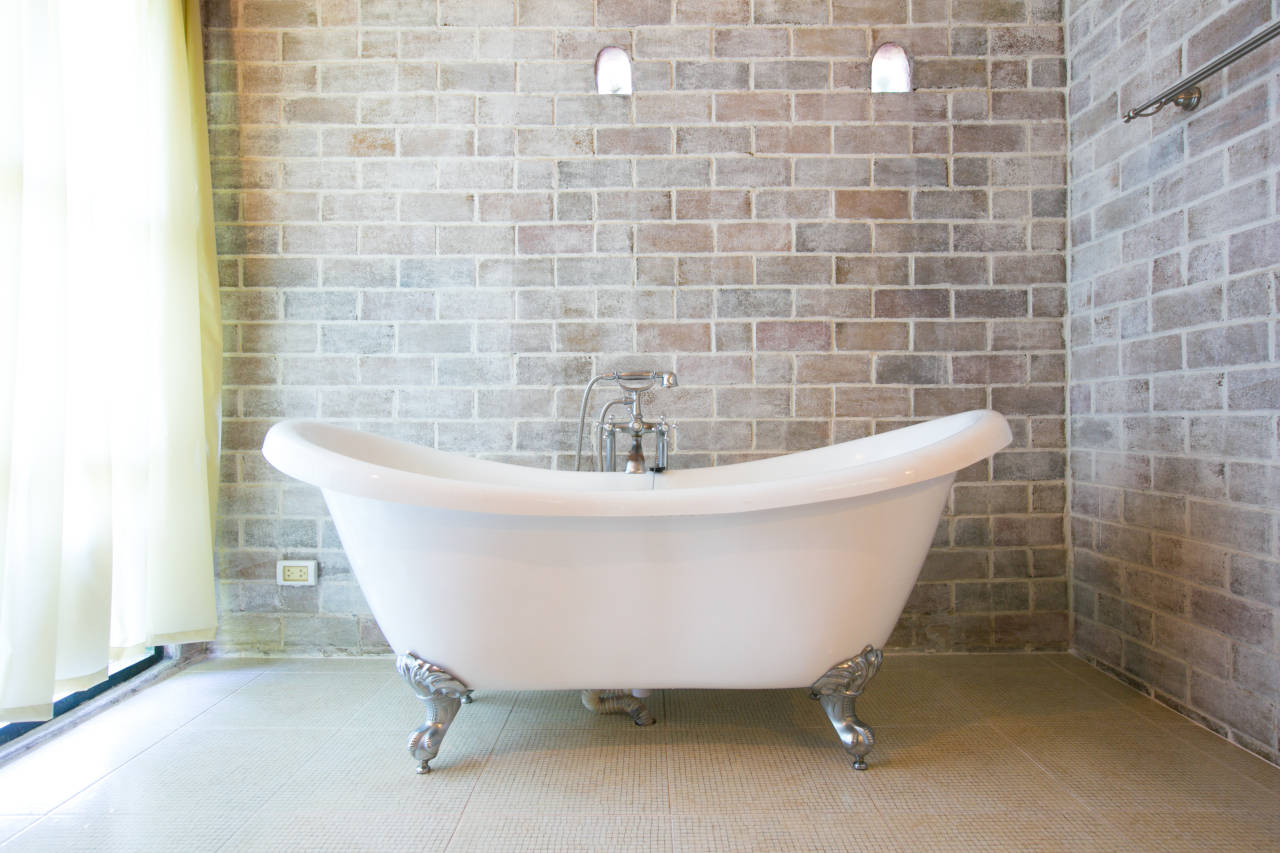 cast iron clawfoot bathtub in a bathroom with brick walls