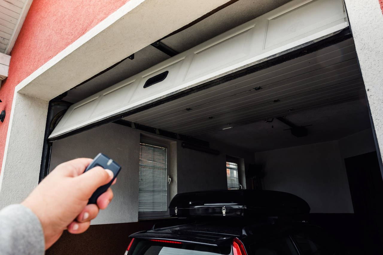 person opening garage using a garage door opener remote