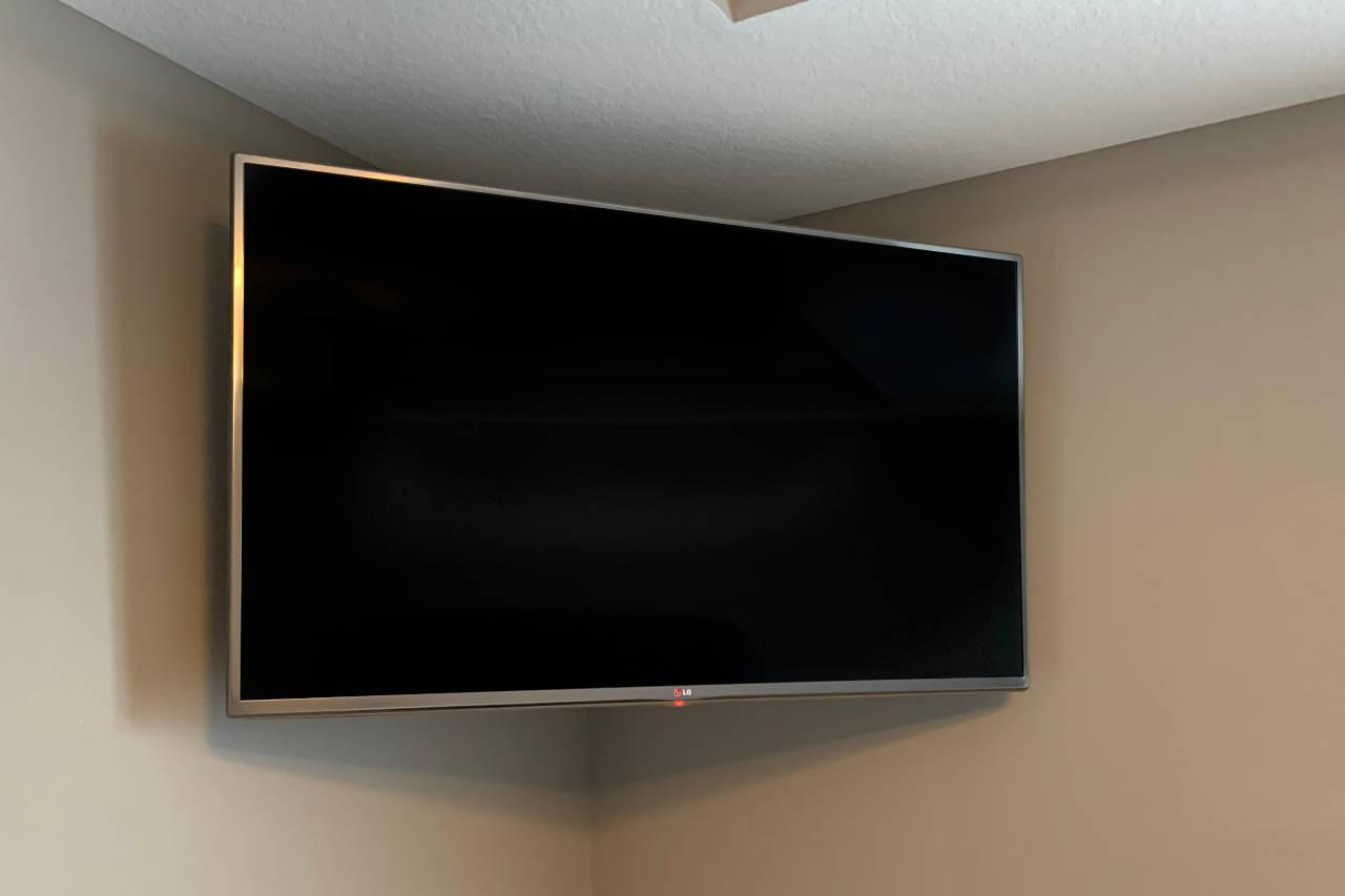 flat screen tv mounted in a corner using an articulated swivel bracket
