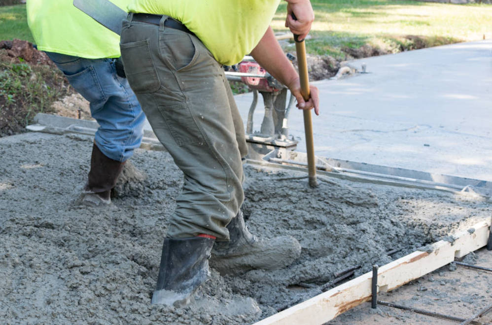 Contractors pouring and finishing a concrete slab