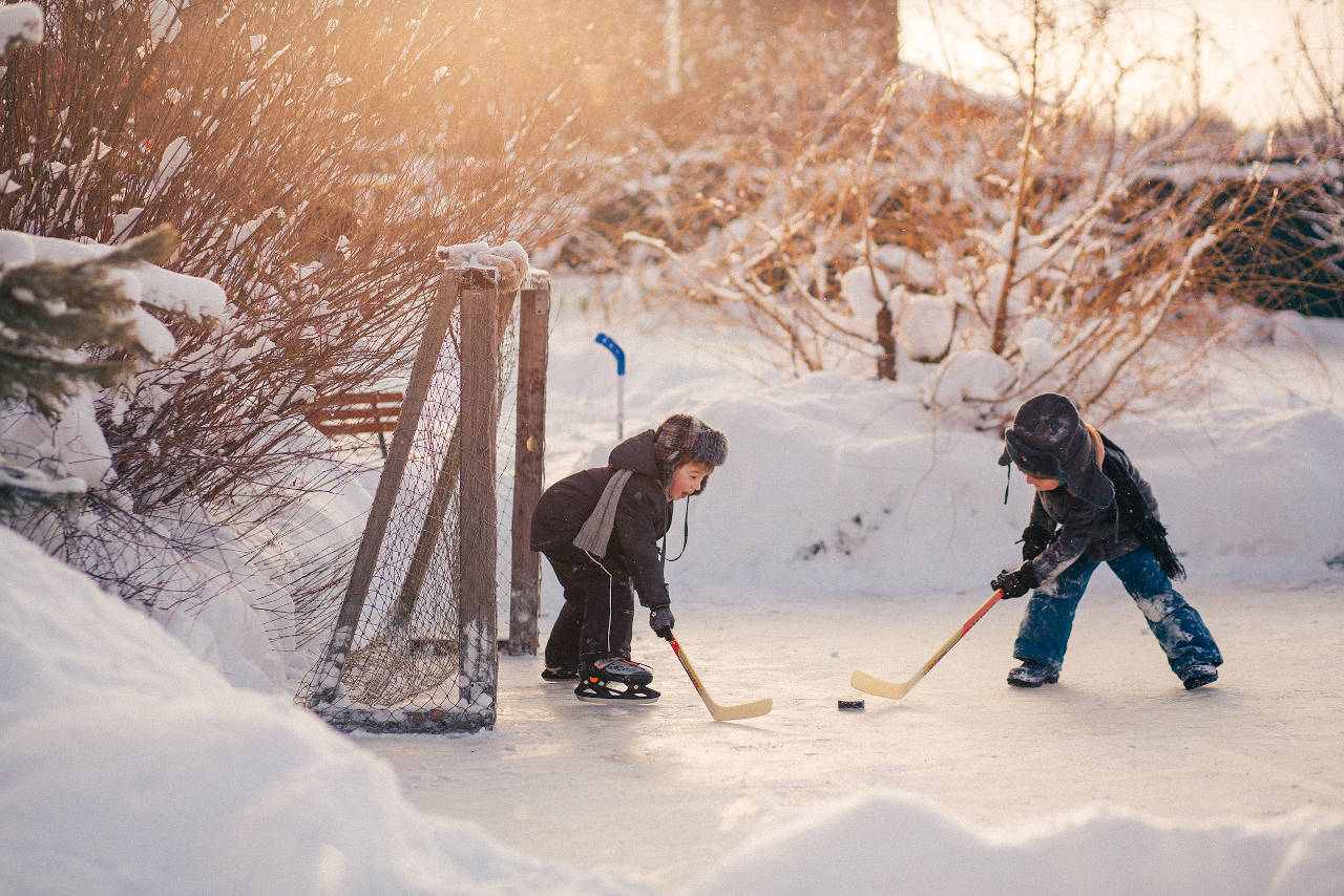 Kids playing hockey on a backyard ice rink