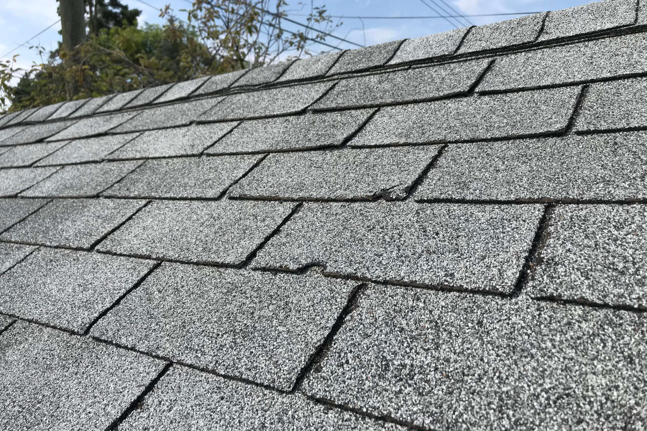 asphalt shingles with large cracks on an old roof in need of repair