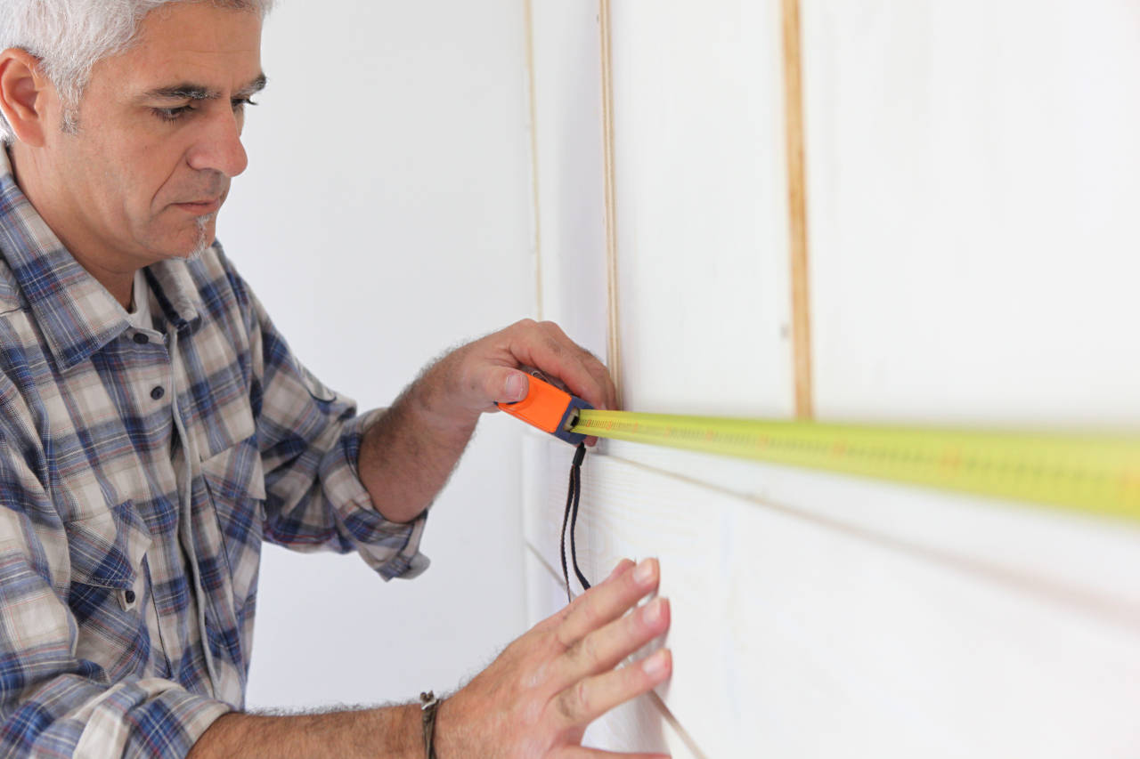 Homeowner using a tape measure to measure a wall