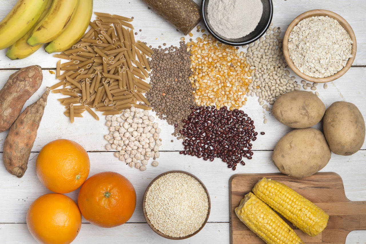 platter of food high in complex carbohydrates, including bread, pasta, starches, beans, and fruits