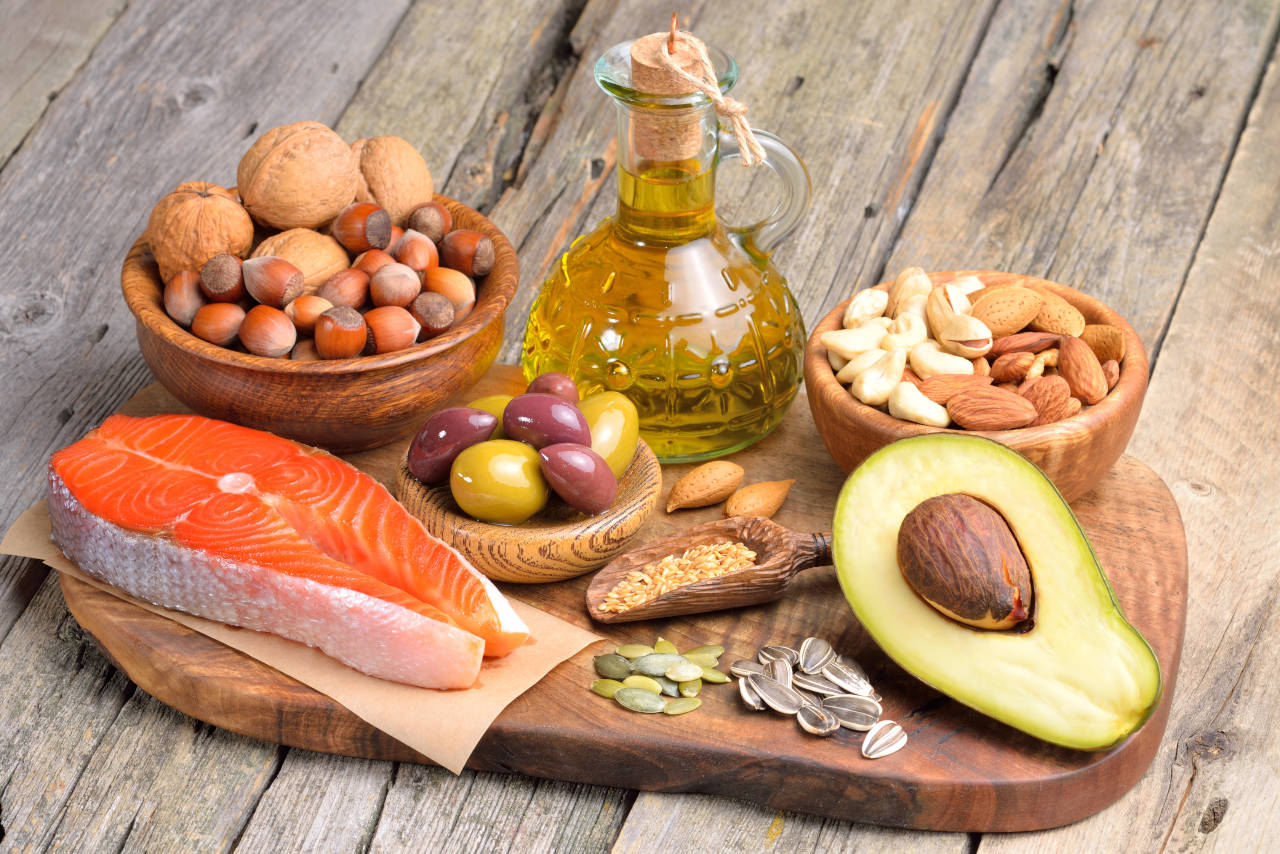 platter of foods high in healthy fats, including fish, walnuts, almonds, and avacado