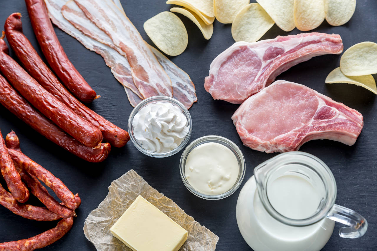 Platter of foods high in saturated fats, including butter, cream, vegetable oil, and lamb