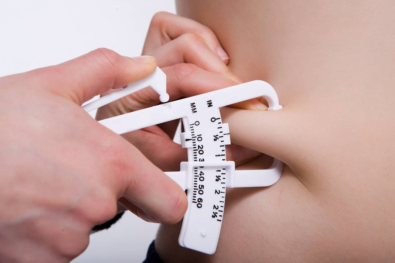 Taking a skinfold measurement with calipers to calculate body fat